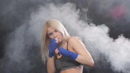 duruş : Long-haired blonde kickboxing woman training in fitness studio, slow motion. Aggressive stance, ready to repel the attack. Stok Video