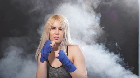 duruş : Attractive blonde woman fighter in boxing bandages posing in defense boxer stance isolated on dark background in sport and fitness exercise workout. Stok Video
