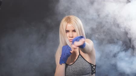 duruş : Young attractive kickboxing female fighter with blonde hair practicing punches. Kickboxer in blue bandages throwing punches for the fight. Dark smoky background Stok Video