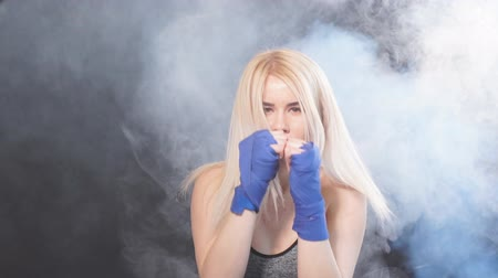duruş : Portrait of attractive blonde woman fighter in boxing bandages posing in defense boxer stance isolated on dark background in sport and fitness exercise workout.