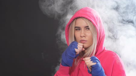 punching bag : Young beautiful woman in pink sportswear with hood on, practicing punches while standing in dark gym. Sport and training concepts. Stock Footage