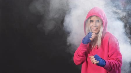duruş : Concentrated blonde kickboxing woman in pink sweatshirt with hood on training in fitness studio over dark smoky background. Aggressive stance, ready to repel the attack. Stok Video