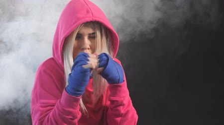 duruş : Female boxer in pink hoodie prepares to punch at a boxing studio. Woman boxer in motion