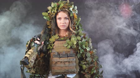 stealth : Heavily armed female soldier in battle helmet and ghillie suit holding assault rifle isolated on dark smoky battlefield. Paint ball and laser tag sport games