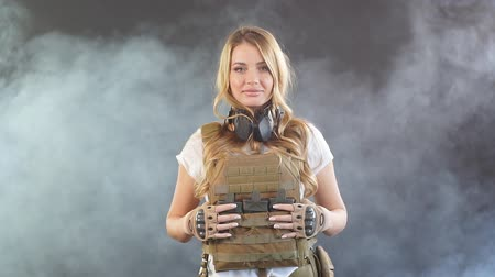 marksman : Gorgeous young woman with long blonde hair wearing Military gear, posing isolated in studio over dark background