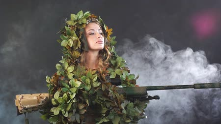 invisible : Camouflaged woman sniper in ghillie suit posing with rifle in foggy night. Slow motion. Special Weapons and Woman Concept.