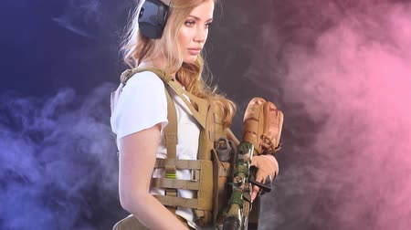 orvlövész : Beautiful caucasian female private military contractor with long blonde hair, dressed in tactical uniform, armed with riffle posing isolated in studio over black foggy background Stock mozgókép