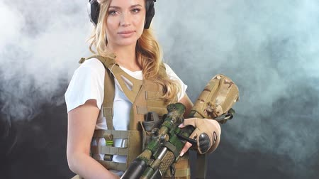 marksman : Skilled blonde female soldier with rifle in hands standing in military outfit in smoky darkness. Woman, Military Service and firearm concept