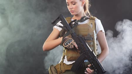 fire suit : Portrait beautiful blonde female soldier dressed in plate carrier and warbelt. Women, army, weapon, technology and people concept. Black smoky background.