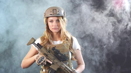 marksman : Skilled blonde female soldier with rifle in hands standing in military outfit in smoky darkness. Woman, Military Service and firearm concept. Slow motion Stock Footage