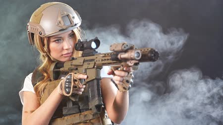 slayer : Calm concentrated woman marksman in sniper gear holding rifle in hand at dark smoky background, Slow motion