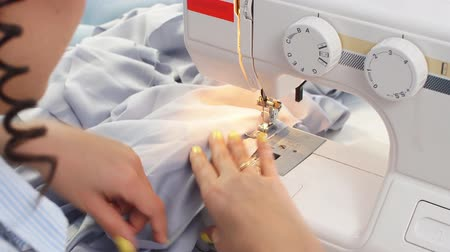 el sanatları : Close-up of hand seamstresses working on a new order using a sewing machine. Clothers Designer