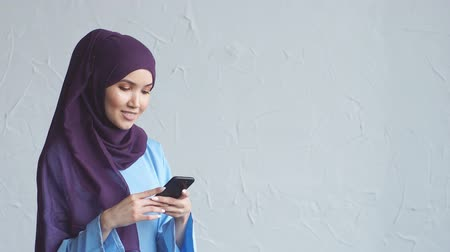 öz : Young Muslim woman is chatting with her friends. Smartphone in the hands of a beautiful arabian woman wearing a hijab