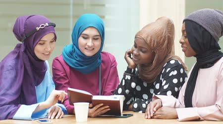 akademický : Happy muslim multiethnic girls students discussing book in library. Dostupné videozáznamy