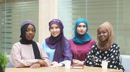 unie : Group of beautiful young muslim business women wearing hijabs of different colour, are sharing info, sitting together at table in business centre