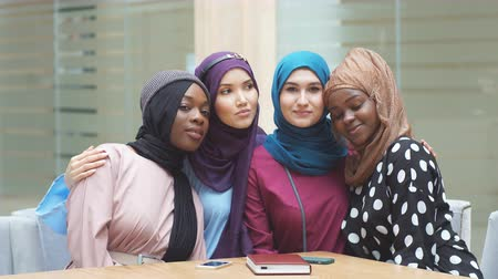 muslim leader : Portrait of multiracial group of muslim women dressed in national dresses and hijabs of bright colours in modern shopping centre.