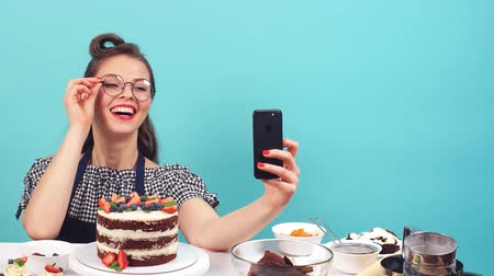 calorias : Cute pastry girl doing selfie with cupcake in hand on turquoise background in Studio Stock Footage