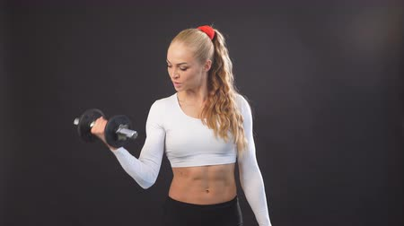 немой : Strong muscular woman holding dumbbells and posing to the camera. Well-built female athelete with flat stomach