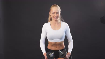 weightlifting : Pleasant cute woman leraning to train with dumbbells. Professional personal trainer showing master class, workout. Isolated black background Stock Footage