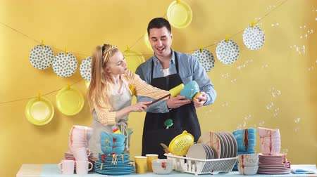 hadr : Attractive young couple dusting the plates. Happy young man and woman using plate like a mirror in the kitchen room
