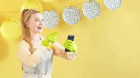 szobalány : Cheerful positive blonde girl with raised finger and smartphone looking at camera. Happy housewife pointing up, holding a mobile phone and looking at the camera