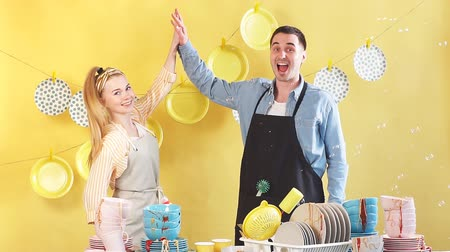 příbory : Beautiful active young hardworking couple is giving high five and smiling in kitchen, isolated yellow background, good job.