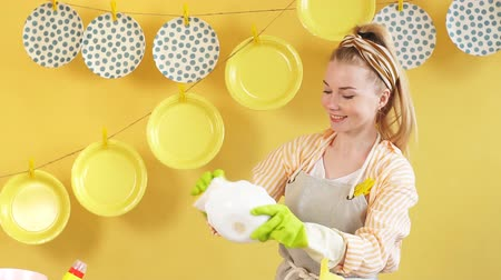 colander : Happy wife enjoying her time in kitchen room. Cheerful woman rejoicing at washing the dishes