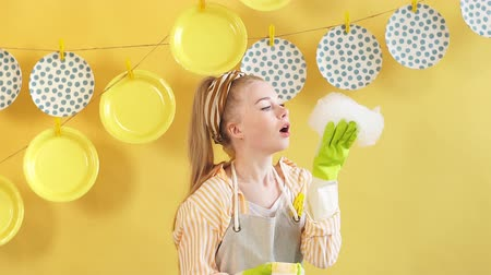 colander : Funny beautiful fair-haired woman blowing the foam from the sponge.