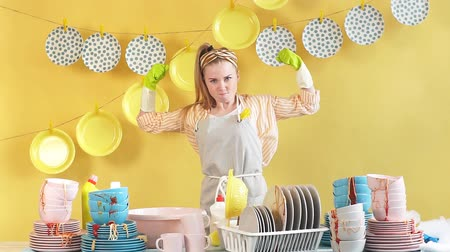 dezenfekte etmek : Cheerful blonde housewife in gray apron in green gloves showing biceps isolated on yellow background. Happiness, Winner of contest.