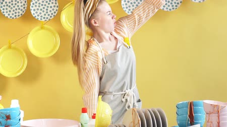 süpürge : Attractive awesome girl in gray apron using brush as a microphone in the kitchen with modern interior. Plates are hanging on the clothespins Stok Video