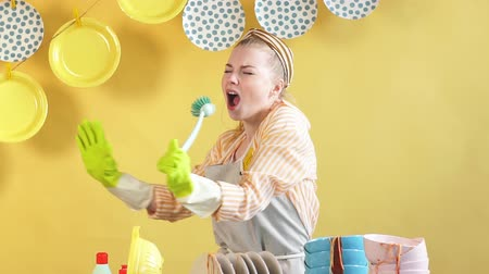 sprzataczka : Attractive girl being in good temper, holding brush as a microphone, giving way to her talent and joy.isolated yellow background. Housewife singing songs like a singer.