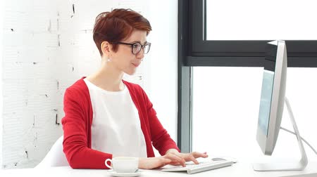 классный : Young woman working in office, sitting at desk, using computer and looking on screen