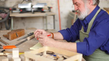 çabaları : Old man is making a sketch of birds house from wood. Concept of diy.