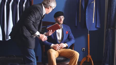 шить : Young, handsome and successful businessman trying on a custom made stylish suit at tailors shop. Dressmaking and Tailoring establishment concept