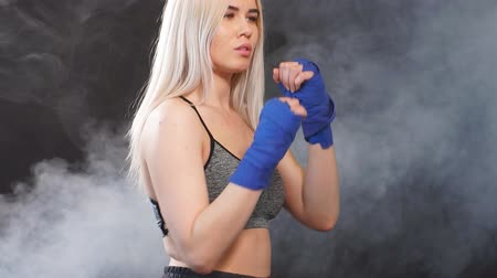 duruş : Attractive blonde woman fighter in boxing bandages posing in defense boxer stance isolated on dark smoky background in sport and fitness exercise workout.