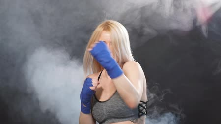 duruş : Blonde female athlete is exercising in defense and attacks on dark smoky background.