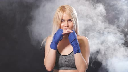 bandage : Attractive blonde woman fighter in boxing bandages posing in defense boxer stance isolated on dark background in sport and fitness exercise workout. Stock Footage