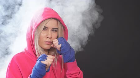 duruş : Long-haired blonde kickboxing woman in pink sweatshirt with hood on, training in fitness studio. Aggressive stance, ready to repel the attack.