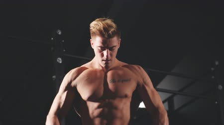 üstsüz : Shirtless white man in sweatpants starting exercise with dumbbell weight in dark gym. Fitness motivation and muscle training concept. Stok Video