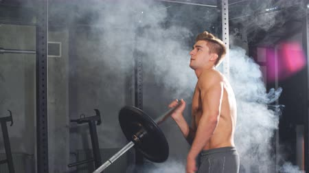 монтаж : Caucasian muscular shirtless bodybuilder, flexing weight plates on iron bar. Weightlifting training.