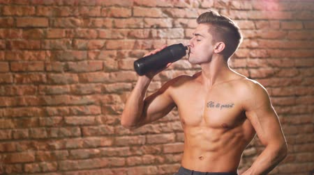 sede : Young sexy athlete With bare torso Drinks water from sports bottle of black color after training