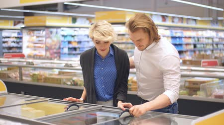 супермаркет : Happy caucasian couple choose frozen foods from the supermarket refrigerator. Family shopping at trading centre in a grocery department. Стоковые видеозаписи
