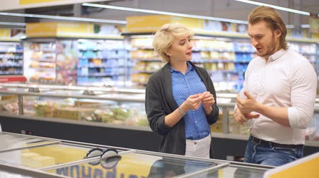 conveniente : Cheerful young couple choose frozen food in the supermarket refrigerator for a family celebration Stock Footage