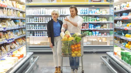 supermarket shelf : Couple in a supermarket shopping equipped with a shopping cart buying groceries and other stuff, they are looking for what they need Stock Footage