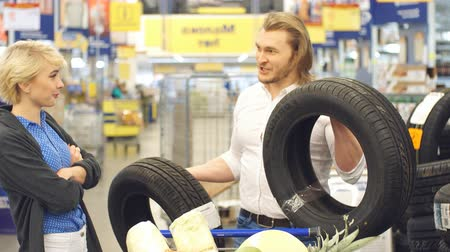покупка товаров : Happy couple make choice with car tires in shopping mall, man choosing the best tire, suggest to buy it to his wife. Стоковые видеозаписи
