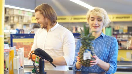 регистр : Young happy couple puts numerous products on cash register for payment. Стоковые видеозаписи