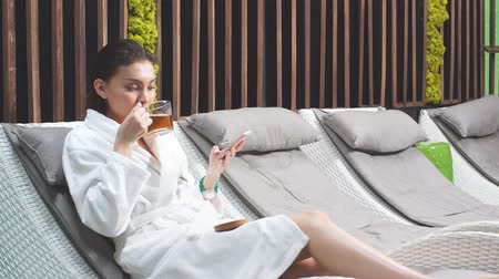 hydratační : Attractive woman drinking fragrant tea in a modern Spa center.