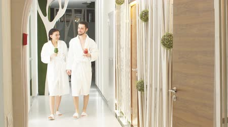acalmar : Two lovers go down the corridor for treatments at the Spa. Healthy lifestyle. Vídeos