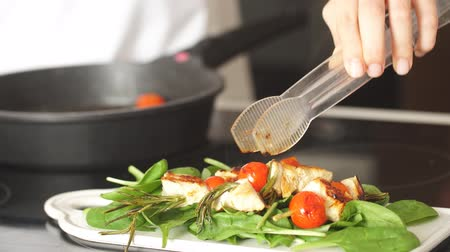 pans : Chicken kebabs served with tomato cherry and greenery on a white chopping board on the kitchen stove