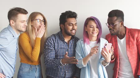crowd together : Group of Multicoloured joyful people standing against white wall. Caucasian woman with violet hair showing photos on smartphone to her diverse friends. Stock Footage